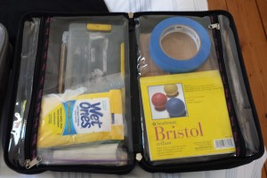 Art supplies neatly packed inside a toiletry bag. Supplies inside include a Plano box containing mediums, Wet Ones, bristol paper pad, small board, and tape.