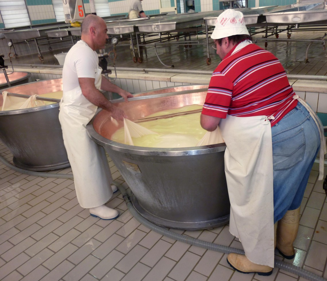 Cheesemakers pull Parmigiano Reggiano out of cauldron on the Italian Days Food Tour